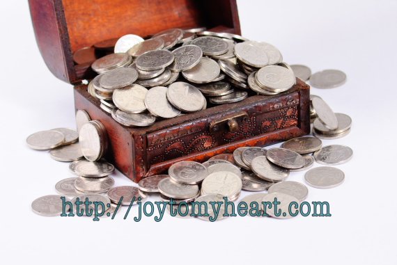 Wooden chest with coins inside isolated on white background